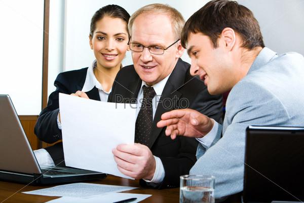 Фотография на тему Команда бизнесменов смотрит на новый бизнес план и обсуждает новые идеи