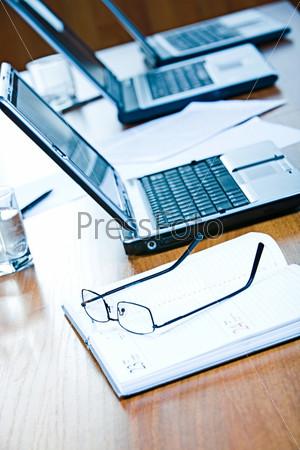 Очки лежат на ежедневнике на фоне ноутбука