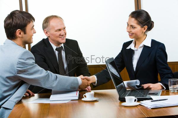 Партнеры по бизнесу пожимают руки за столом после заключения сделки