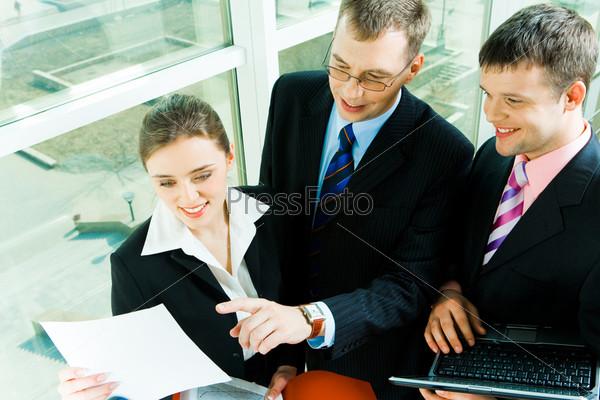Бизнесмен показывает документ коллегам