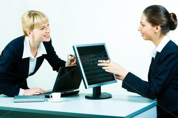 Две женщины сидят за столом в офисе и обсуждают работу