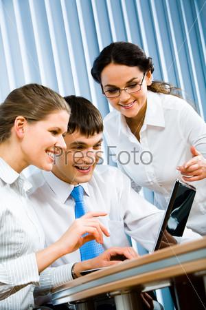 Успешные партнеры по бизнесу смотрят на экран ноутбука во время деловой встречи в офисе
