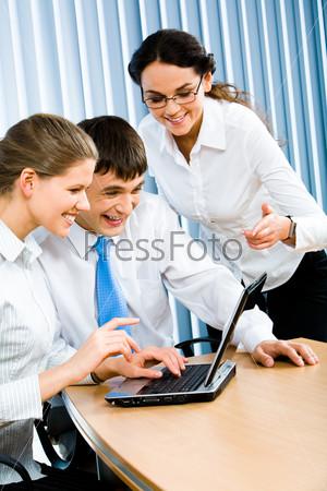 Молодые бизнесмены смотрят на экран ноутбука и смеются