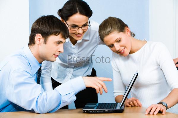 Бизнесмен показывает что-то на экране ноутбука девушкам, стоящим рядом с ним
