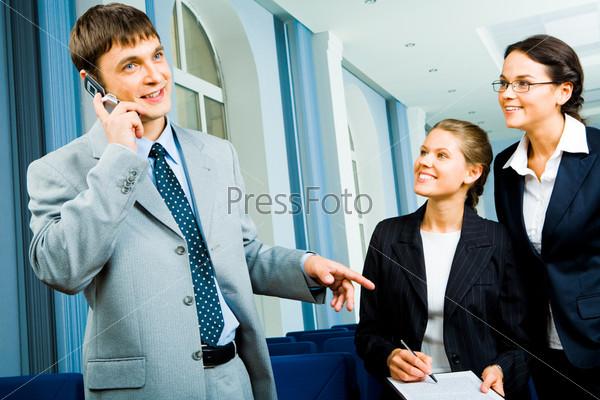 Бизнесмен разговаривает по сотовому телефону, а две девушки в деловых костюмах смотрят на него