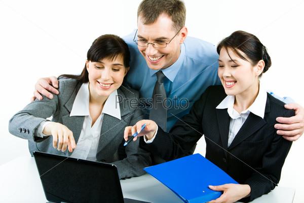 Успешные деловые люди смотрят на экран ноутбука и улыбаются