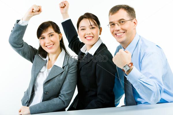 Две девушки и мужчина в деловых костюмах поднимают руки, сжав кулаки, показывая силу единства