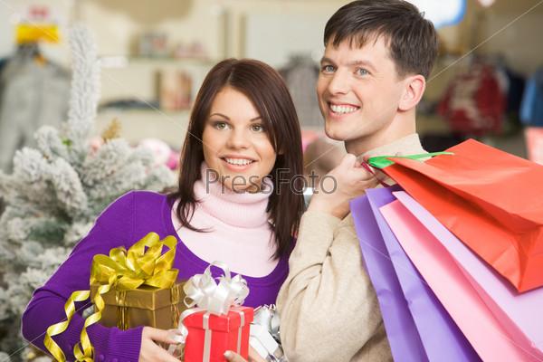 Радостные муж и жена пришли в торговый центр за рождественскими подарками