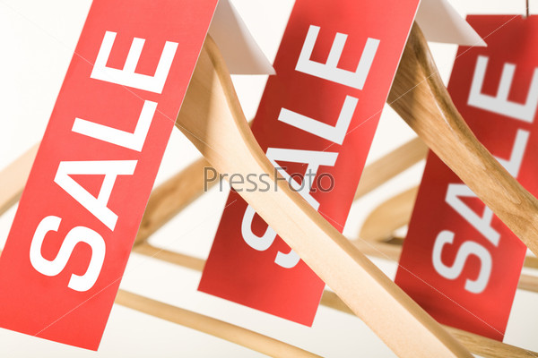 Close-up of red sale labels on wooden hangers in mall or store