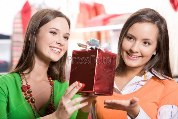 Две симпатичные девушки выбирают рождественские подарки в торговом центре