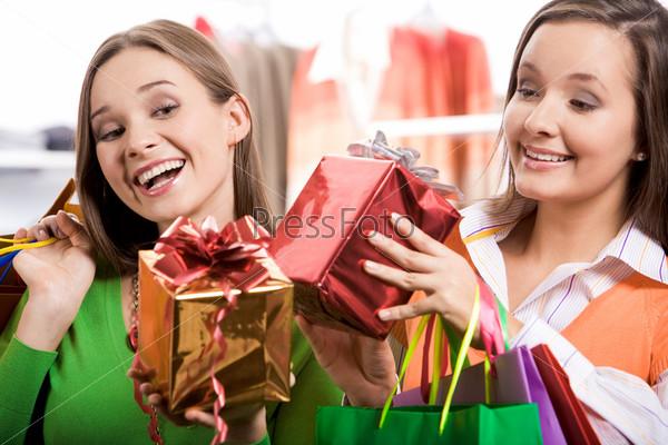 Очаровательные девушки смотрят на подарки в их руках и радостно смеются