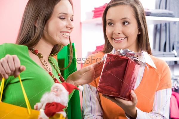 Покупательница смотрят на упакованный подарок, которые ей предлагает консультант
