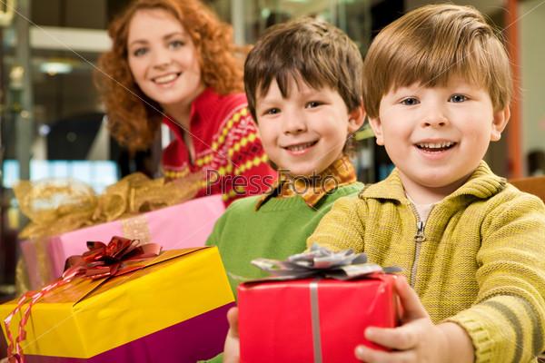 Мальчики с мамой держат в руках рождественские подарки