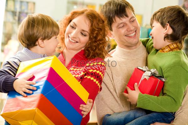 Счастливые родители держат сыновей на руках и улыбаются