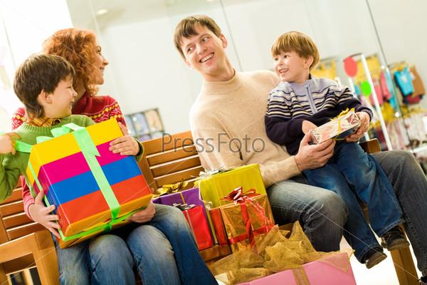Радостные родители с сыновьями сидят в супермаркете рядом с подарками