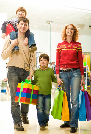 Modern family going shopping in trade center before Christmas time