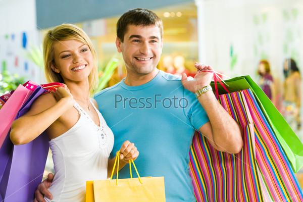 Счастливый мужчина с разноцветными пакетами в руках обнимает свою девушку в торговом центре