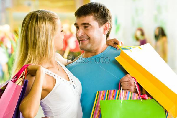 Мужчина и женщина с пакетами для покупок обнимаются в торговом центре