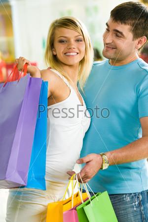 Привлекательный молодой человек смотрит на очаровательную спутницу в торговом центре