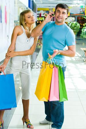 Девушка подслушивает телефонный разговор мужчины в торговом центре