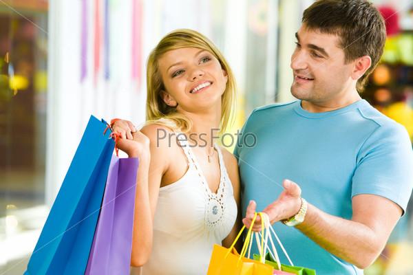 Счастливая пара с пакетами в руках смеется в торговом центре
