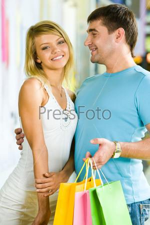 Мужчина держит разноцветные пакеты с покупками и обнимает очаровательную девушку