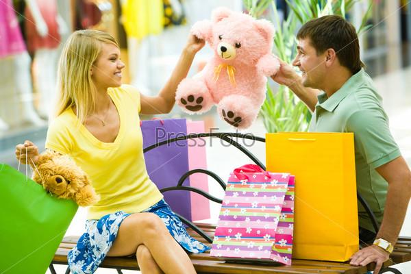 Радостная пара сидит на скамейке в торговом центре и держит розового плюшевого медведя