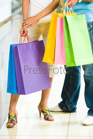 Разноцветные пакеты с покупками в руках молодых людей