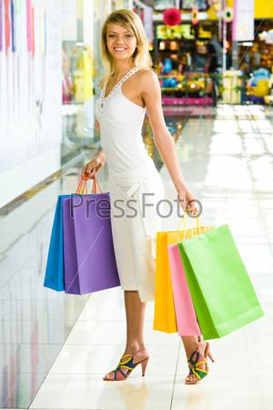 Красивая девушка стоит в торговом центре с разноцветными пакетами в руках