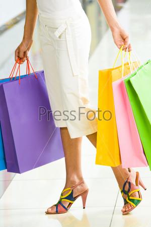 Разноцветные пакеты в руках молодой девушки