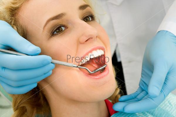 Молодая пациентка во время осмотра стоматологом