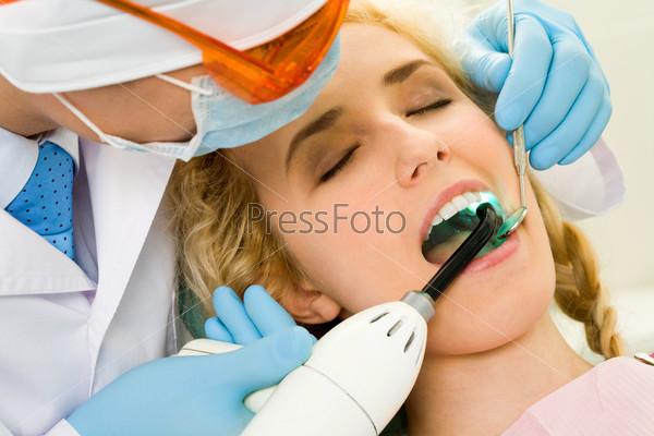 Красивой девушке лечат зубы в кабинете стоматолога