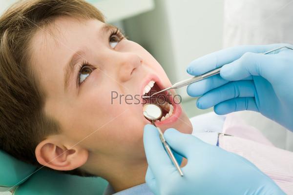Маленький мальчик сидит в кресле на осмотре у стоматолога