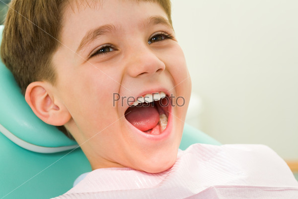 Мальчик с открытым ртом сидит в кресте в кабинете стоматолога