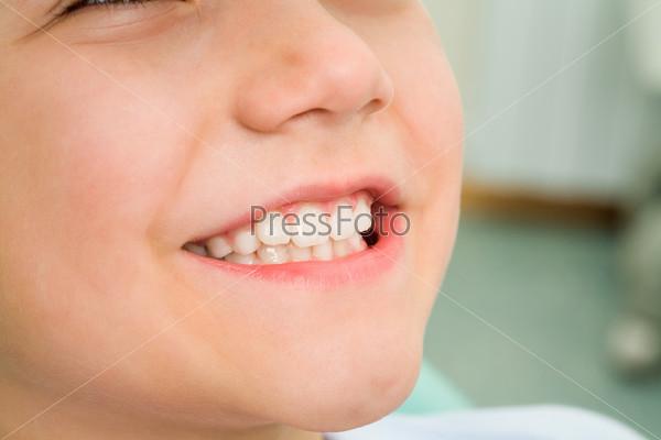 Фотография на тему Маленький мальчик улыбается, сидя в кабинете стоматолога
