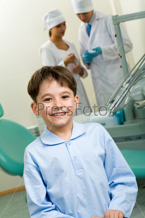 Счастливый мальчик в стоматологическом кабинете на фоне двух врачей