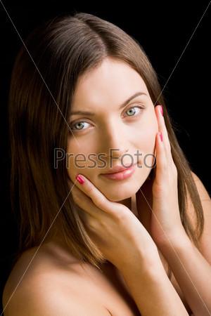 Симпатичная девушка с длинными волосами держит руки около лица и смотрит в камеру
