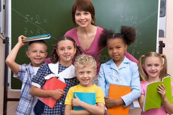 Дружный класс стоит у доски вместе со своей учительницей