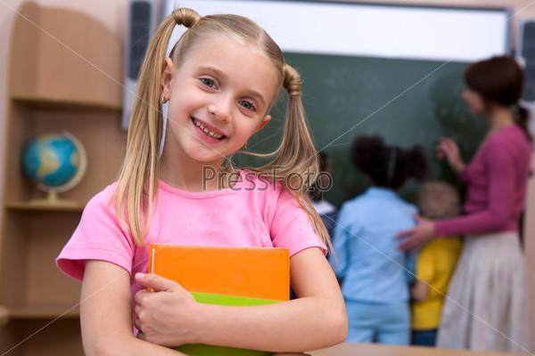 Жизнерадостная школьница на фоне одноклассников и учительницы