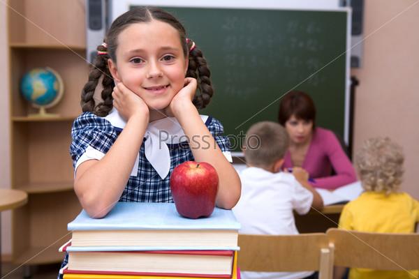 Позитивная девочка стоит в классе облокотившись на стопку учебников