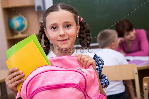 Прилежная ученица собирает школьный рюкзак после занятий