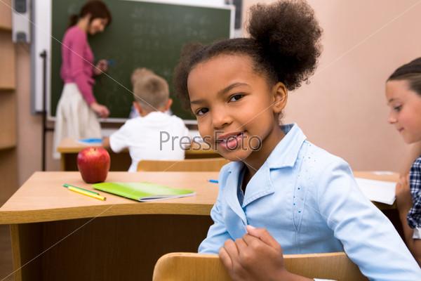 Ученица сидит за партой в классе на фоне школьной доски