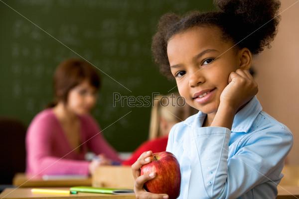 Девочка с красным яблоком в руке сидит за партой и смотрит в камеру