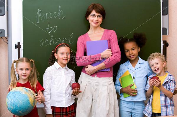 Дети вместе с учительницей стоят у доски
