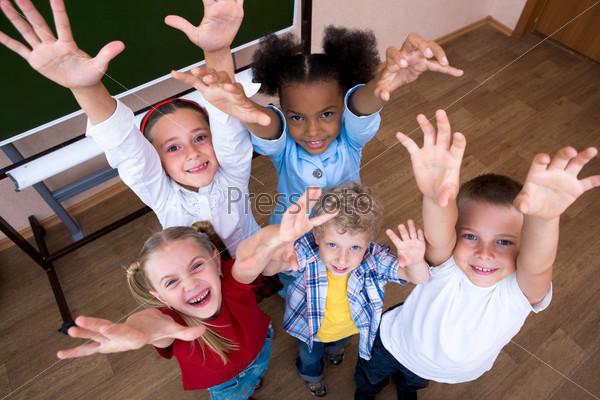 Пятеро детей смотрят вверх подняв руки и смеются