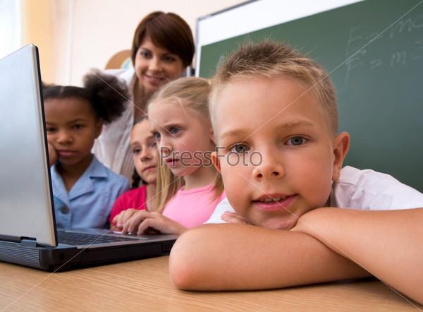 Крупный план школьника за партой на фоне класса
