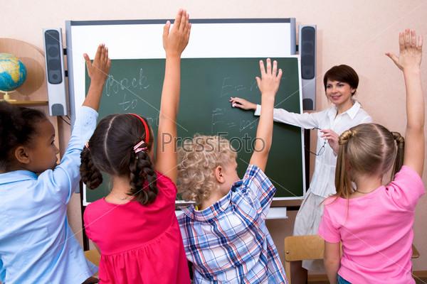 Группа школьников подняв руки стоит глядя на свою учительницу у доски