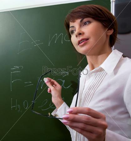 Учительница объясняет урок стоя у классной доски