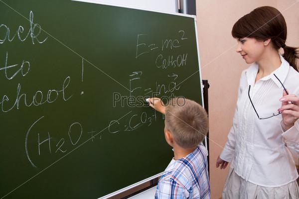 Фотография на тему Учительница наблюдает как ученик решает задачу у доски