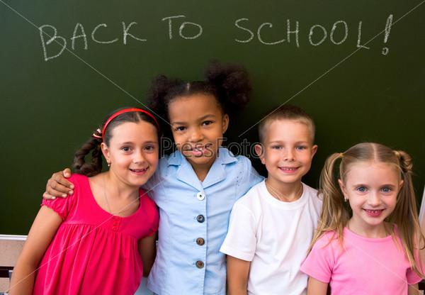 Дружные одноклассники стоят вместе на фоне доски
